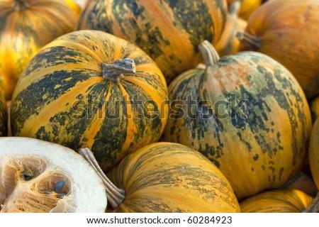 Some pumpkins on farmers market, one pumpkin cut in half - stock photo
