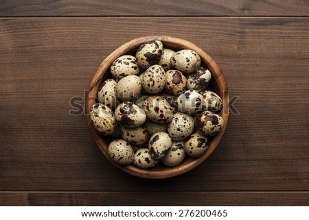 some quail eggs on the brown wooden table - stock photo