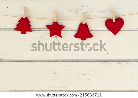 Some red felt Christmas figures hanging with clothing and a white wooden background. Christmas vintage style. - stock photo