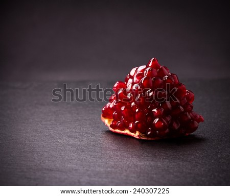 Some red juicy pomegranate, whole and broken, on black slate plate - stock photo