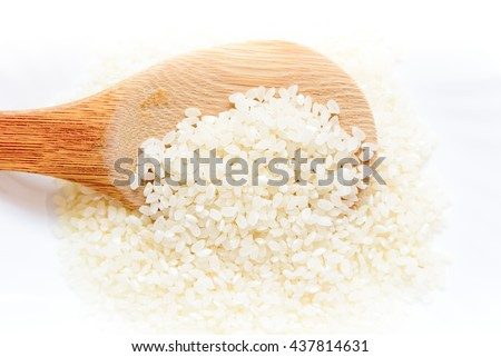 Some rice is on a white plate.Some rice is on a wooden spoon.