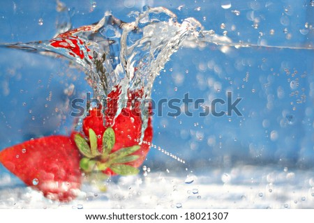 Some ripe and juicy red strawberries plunging into some water.  Shallow depth of field. - stock photo
