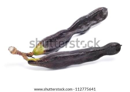 some ripe carobs on a white background - stock photo