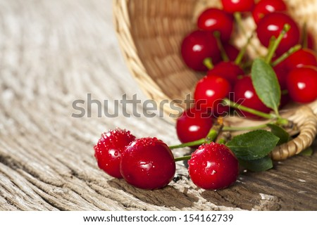 Some ripe Cherries with sparkling Water Drops in small Basket on a old Wooden Table - stock photo