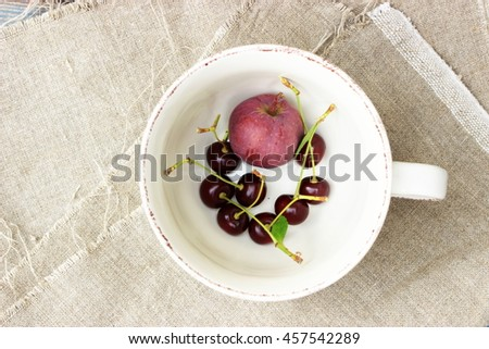 Some ripe dark red cherry and a pink apple in a vintage white cup on rough linen cloth. Amazing beautiful composition with romantic summer theme in a rustic setting. Shabby chic - stock photo