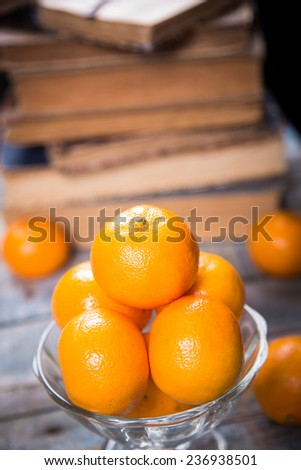 some ripe fresh mandarins in dish on wooden background near the book - stock photo