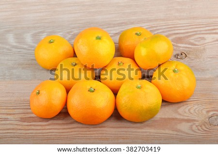 Some ripe mandarin fruit on wooden background - stock photo