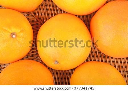 Some ripe orange fruit on wickered background - stock photo