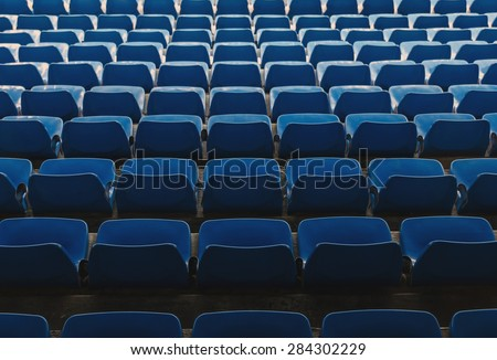 Some rows of empty seats in blue as seen from above - stock photo