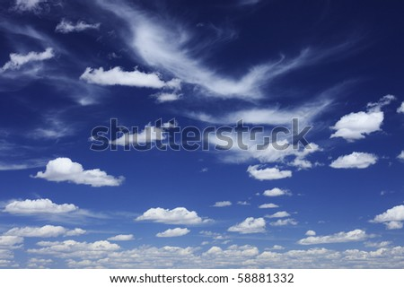Some scattered wispy and puffy clouds in a blue sky. - stock photo