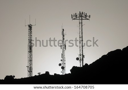 Some Silhouetted Antennas on the top of a Hill - stock photo