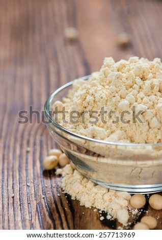 Some Soy Flour on rustic wooden background (close-up shot) - stock photo