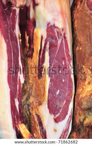 some spanish serrano hams hanging on a bar - stock photo