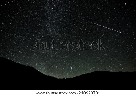Some stars in the night of San Lorenzo with beautiful mountain on the Dolomiti. Real falling stars with darkness sky - stock photo