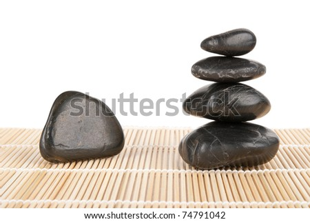 Some stones lie pyramid on mat isolated in white