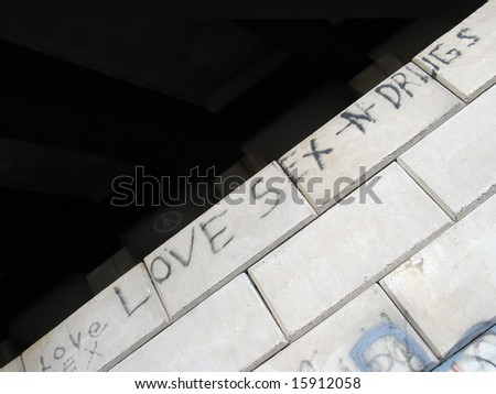 Some street graffiti that reads LOVE SEX AND DRUGS - stock photo