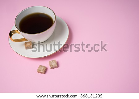 some sugar cubes with coffee cup on pink background - stock photo