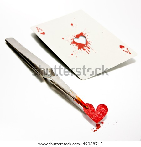 Some tweezers holding a paper heart, just removed from an ace of hearts. - stock photo