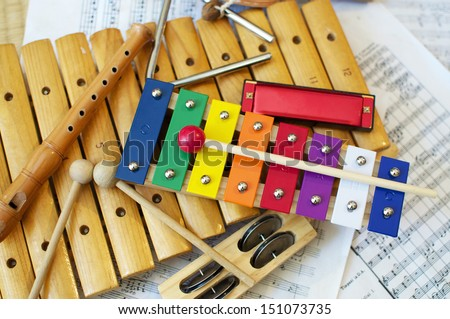 Some typical, colorful music instruments as used mostly by children. The musical score in the background is in the Public Domain.  - stock photo