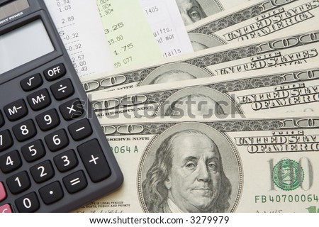Some 100 US dollars cash with some bills and a grey calculator.