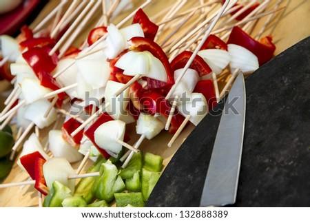 Some vegetables on a brochette. Knife. - stock photo