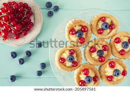 Some vol-au-vent with blueberries and red currants on a cake stand over a robin egg blue wooden table. Vintage Style. - stock photo