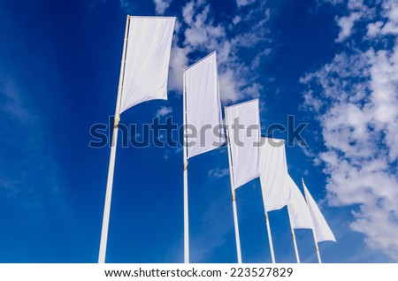 Some white ad banners waving on the sky - stock photo