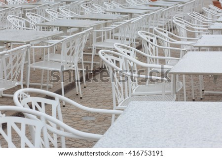 some white tables and white chairs outside. natural light, selective focus.  - stock photo