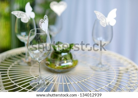 Some wine glasses decorated with paper butterflies - stock photo