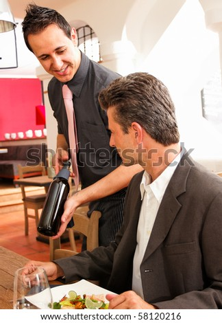 some wine please - waiter offers a bottle of wine - stock photo