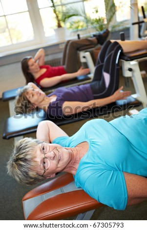 Some women doing crunches in a gym - stock photo