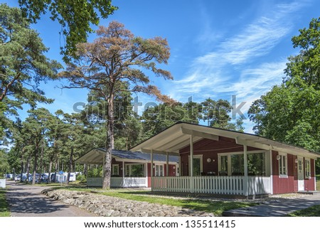 Some wooden camping lodges in a forest caravan park near to Torekov in Sweden. - stock photo