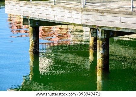 Some wooden pillars under a pier. Water is clam and still.
