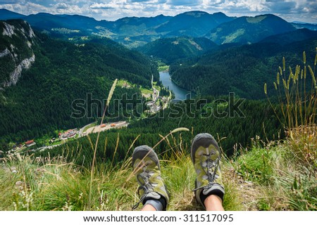 Somebody is sitting at the edge of cliff in mountains, showing his feet wearing hiking shoes. First person shoot. Retezat area, Carpathians, Romania - stock photo