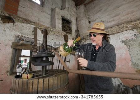 somellier with wine bottle in a old cellar - stock photo