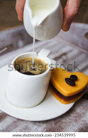Someone adds milk to black coffee, and heart shaped mocca cake - stock photo