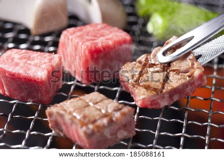 Someone cooking beef on the barbecue and flipping them over. - stock photo