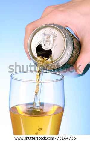 Someone fill glass with beer on blue background - stock photo