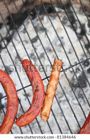 Someone forgot four sausages on a grill, where the coal burn out. - stock photo