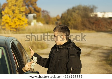 Someone from the car is offering money to the boy - stock photo