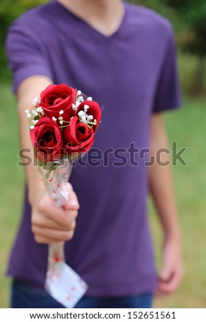 Someone giving out roses towards the camera   - stock photo