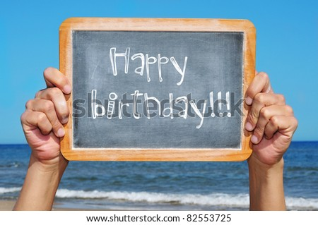 someone holding a blackboard with the sentence happy birthday written in it - stock photo