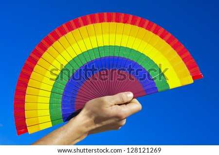 someone holding a hand fan painted with the colors of the gay pride flag over the blue sky - stock photo