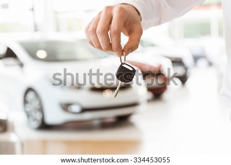 Someone holding car keys by his fingertips at car showroom - stock photo