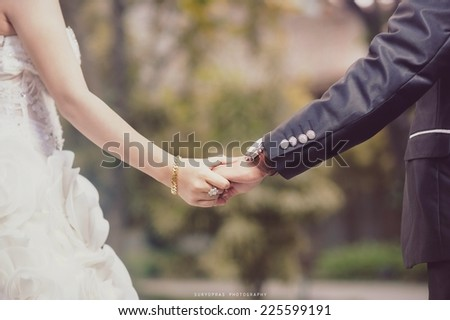 Someone in a wedding dress holding someone else's hand. - stock photo