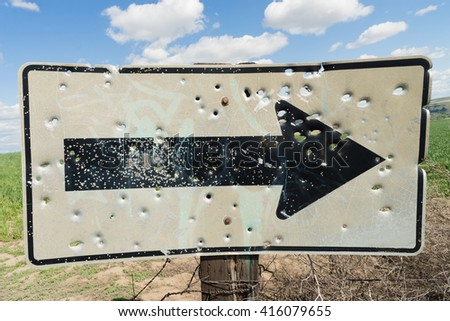 Someone or several people have damaged a road sign by shooting it - stock photo