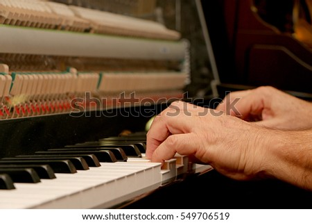 Someone plays piano, close up piano, white and black keyboard