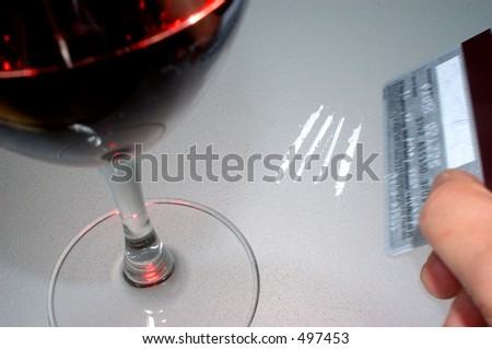 Someone using a platinum card to cut up cocaine. in muted cold tones - stock photo