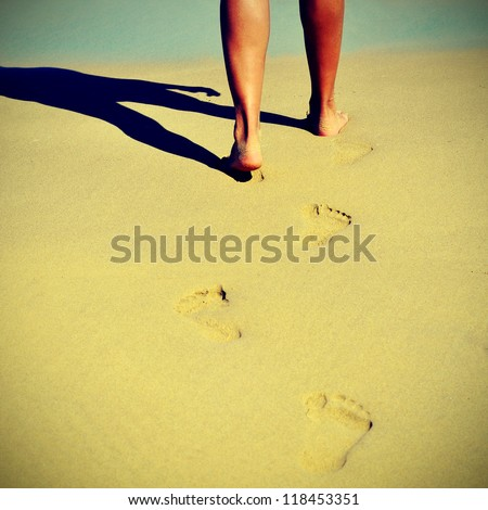 someone walking on the sand of a beach in the summer with a retro effect - stock photo