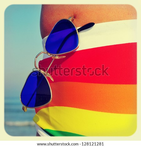 someone wearing a rainbow swimsuit and heart-shaped sunglasses on the beach, with a retro effect - stock photo
